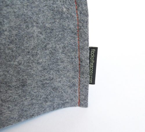 closeup of industrial wool felt in blue-grey with flock of tea cosy label