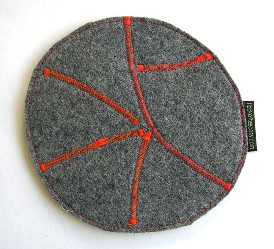 Industrial wool felt hotpad with orange zig-zag stitching.