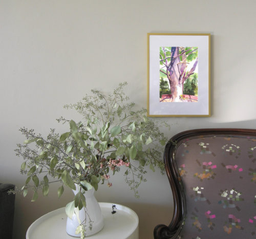 Framed painting of pine tree on wall above armchair