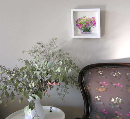 Original watercolour painting of 50 colorful freesia flowers in white frame on wall above armchair and sidetable