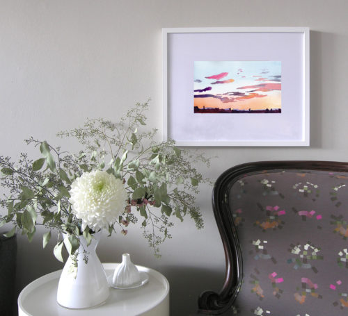 Framed watercolor painting of sunset clouds seen on wall above armchair