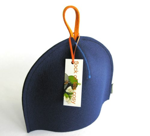 Small modern tea cozy in indigo blue wool felt with orange hang-tab