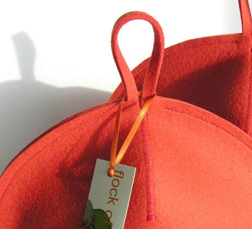 closeup of wool felt tea cosy in coral orange